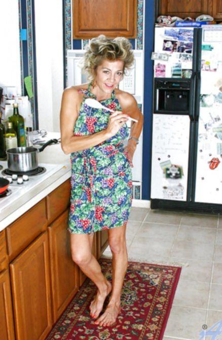 Стройная мамка с небритой пиздой позирует голышом на кухне и кайфует