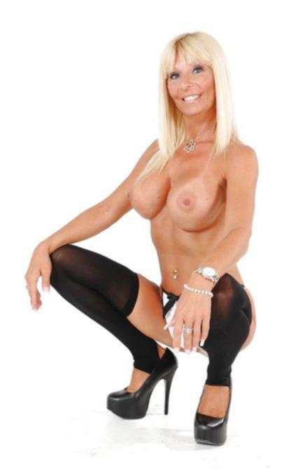 Обалденная блондинка в возрасте снимает трусики на камеру фотографа