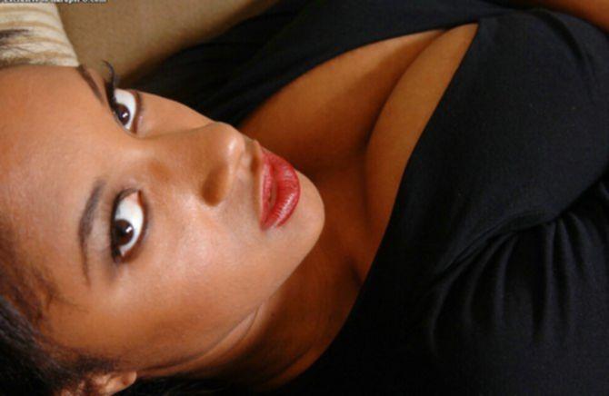 Сексуальная темнокожая девушка с красивыми титьками позирует в комнате
